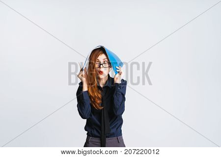 surprised red-haired girl with glasses holds a blue folder with documents on her head