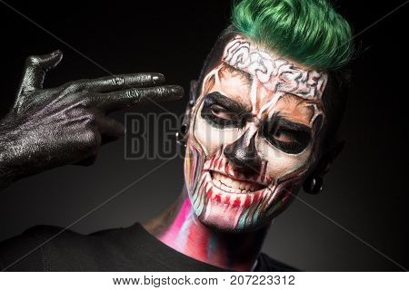 Close up portrait of a man with mystical halloween makeup. Face art concept, man with green hair and skeleton face isolated on black background.