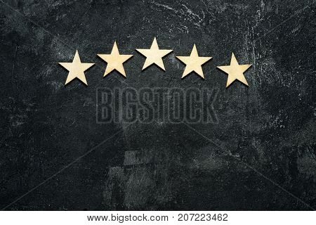 Five wooden stars located in the form of an arch or arc in the upper part of a dark cement background. Conceptual of service rating and quality of trade. Top view copy space for your text.