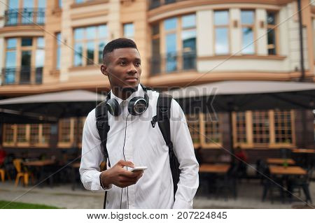 View of african male walking at street searching location on map in smart phone, looking away. Traveler male with bag and headphones around neck using call phone. Electronic map, navigation.