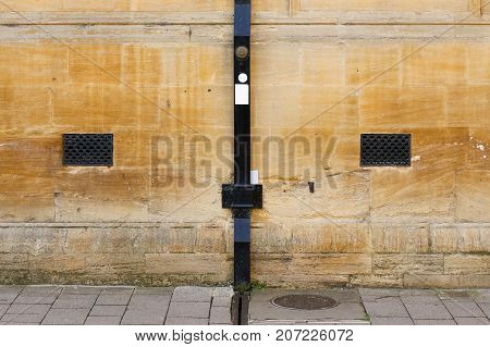 Black Painted Rain Drainage On Sand Stone Wall With Ventilation Holes