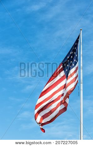 American flag waving on blue sky background in Key West USA on sunny day. National symbol citizenship and patriotism concept. Pride freedom and unity.