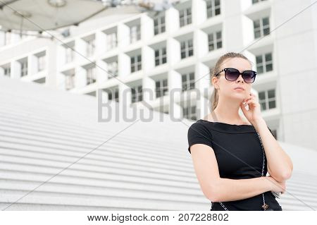 Woman in sunglasses posing on concrete stairs and building in Paris France. Ambitions and success concept. Architecture and design.