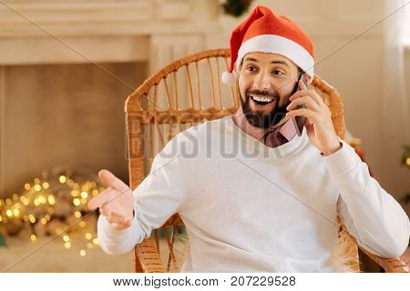 Surprising turn of events. Handsome bearded man in Santa hat sitting in a rocking chair and talking on the phone while looking surprised by something told by interlocutor