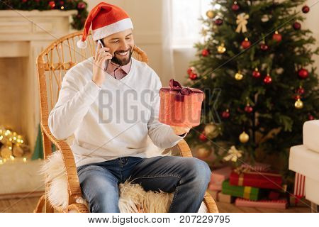 Thanking for present. Cheerful young man in Santa hat sitting in a rocking chair in a room with Christmas decorations and talking on the phone while holding gift box
