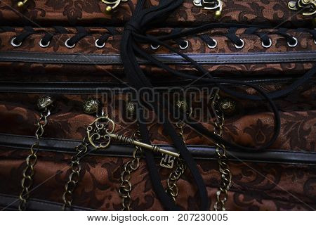 vintage bronze key on the background of beautiful fabrics with decorative elements