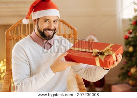 Present for the dearest. Pleasant handsome man in a Santa hat sitting in a rocking chair and poising with a gift box