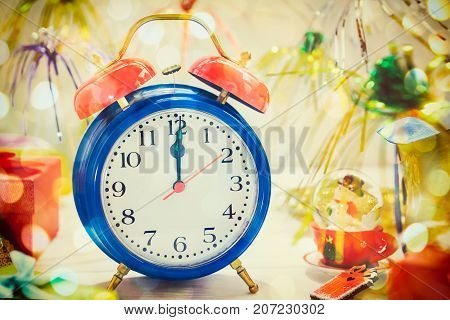 Close up bright clock with midnight time, christmas decorations and gifts on the blurred background. Colorful New year background. Vintage postcard. Space for text. Selective focus.