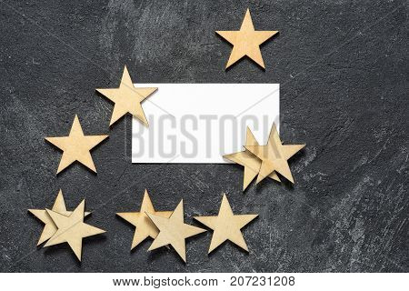 top view of a blank white business card with copy space for your text on a black textural cement background with a group of wooden stars. the highest quality business concept.