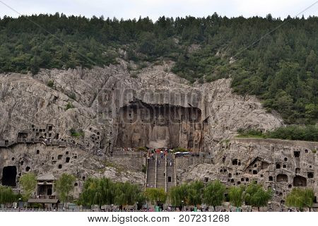 Tourist Visiting Longmen Grottoes, That's Famous For Its Thousands Of Holes Filled By Buddha Statues