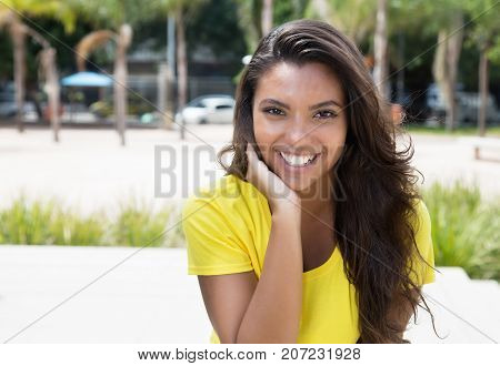 Flirting latin woman in yellow shirt looking at camera outdoors in the summer