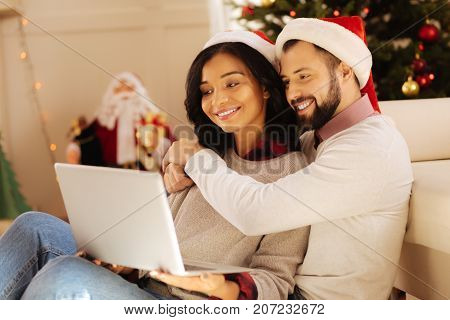 Sweet bonding. Charming international couple in Santa hats sitting on the sofa, cuddling and watching a film on laptop while smiling happily