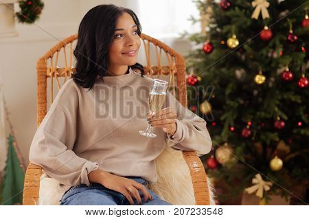 Pleasant ambience. Pleasant dark-haired woman sitting in a rocking chair in a room with a Christmas tree, holding a glass of champagne and looking into the distance
