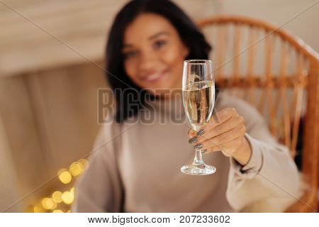 Cheers to you. The focus being on the glass of champagne in the hands of a pleasant dark-haired woman sitting in a rocking chair and smiling