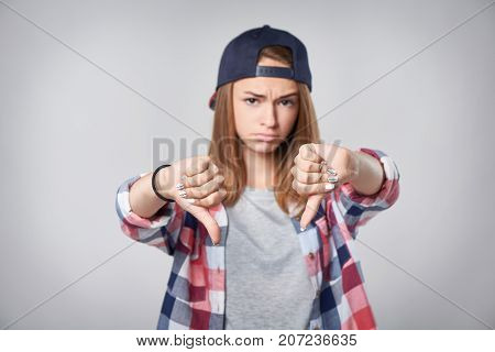 Closeup of discontent teen girl in checkered shirt and baseball cap showing double dislike gesture, over grey background. Shallow depth of field, focus on gesture