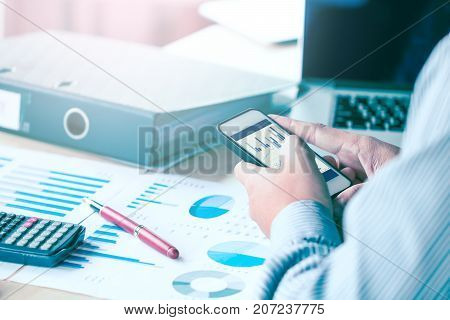 Businessman Hand Looking Data Result At Smartphone And Analysis On Desk At Office Room.
