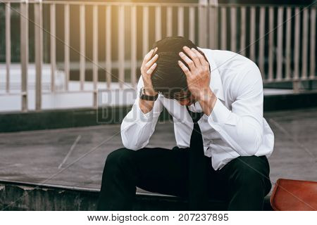 Asian Young Businessman Stress Sitting In Front Of With His Hands Covering His Head Against.