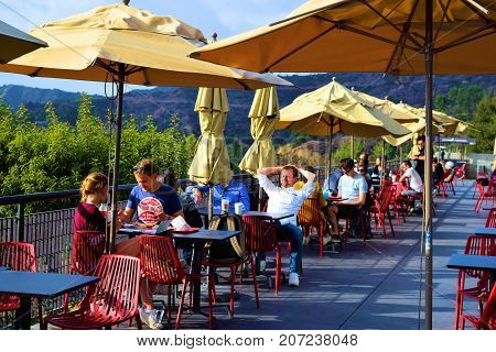 October 3, 2017 in Los Angeles, CA:  People seated on outdoor café seating with tables, chairs, and umbrellas taken at the Griffith Observatory where people can dine the Café at the End of the Universe while enjoying a view of the city and Griffith Park