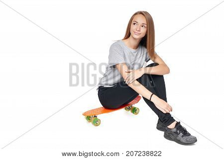 Teen girl in full length sitting on skate board looking away at blank copy space, isolated on white background
