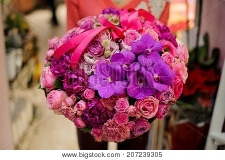 Extremely bright and beautiful bouquet of pink and purple flowers in woman hands. No face close up