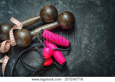 Bright sports concept. Sports equipment as dumbbells expander with pink handles and centimeter tape on a dark black cement background top view with a copy space.