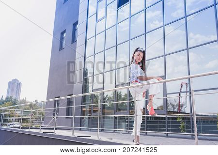 Young african american woman leaning on guardrails near modern building