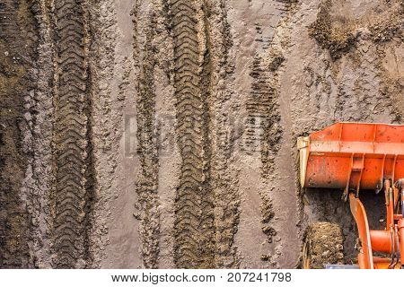 top view of a bulldozer bucket standing on a washed muddy road with prints of protectors construction equipment on wet ground.