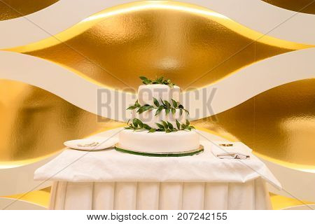 Elegant  White Multi Tiered Wedding Or Birthday Cake Decorated With Fresh Green Leaves On The Table