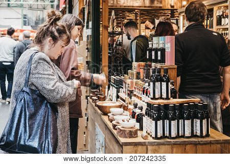 LONDON, UK - SEPTEMBER 30, 2017: Women try olive oil and vinegar at a market stall in Borough Market, one of the largest and oldest food markets in London.
