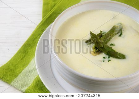 white asparagus cream soup with green asparagus heads garnish in a bowl green napkin white table closeup with selected focus and narrow depth of field