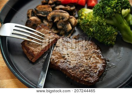 beef steak is cut with knife and fork with vegetables like broccoli mushrooms and tomatoes low carb diet dinner on a dark gray plate selected focus narrow depth of field