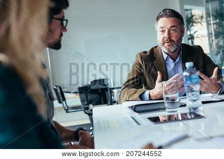 Businessman explaining new business ideas to peers. Startup business team meeting in office conference room.