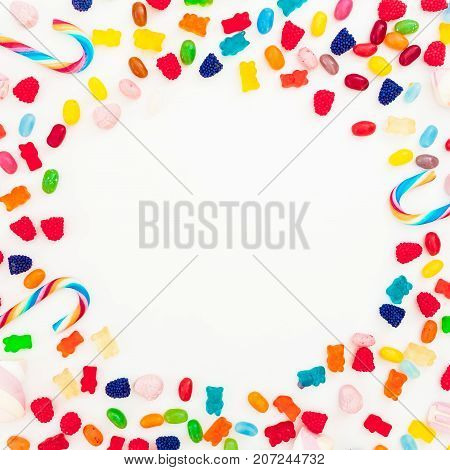 Round frame with assorted colored candies on white background. Sugary concept. Flat lay, top view