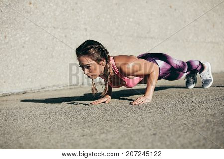 Healthy and muscular young woman doing pushups outdoors. Fitness female doing core exercise in morning.