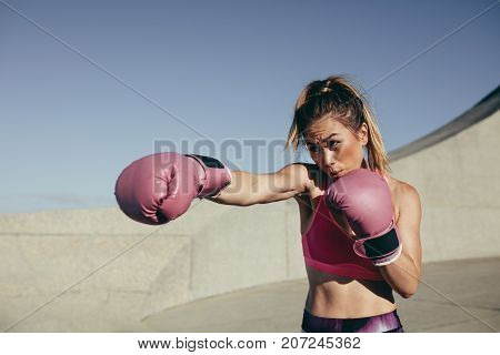 Sportswoman wearing boxing gloves training boxing outdoors. Female boxer practicing boxing.
