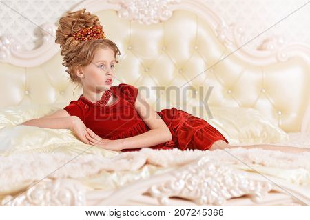 Cute little girl in red velvet dress with retro hairstyle lying on beige couch