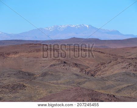 High ATLAS MOUNTAINS range landscape in central MOROCCO seen from location near Ouarzazate city in central part of country, clear blue sky in 2017 warm sunny winter day, northern Africa on February.