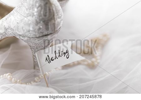 Silver bridal shoes decorated with lace and composed with pearl necklace on veil with flag saying Wedding.