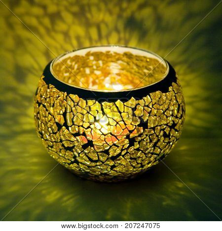 A beautiful candlestick ball of yellow  glass with rays of light, with a glowing candle inside