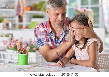 Portrait of a happy father and daughter drawing picture