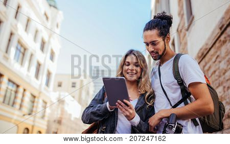 Tourists using navigation tools to explore the city. Man and woman exploring the city with travel accessories.