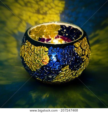 A beautiful candlestick ball of yellow and blue glass with rays of light, with a glowing candle inside