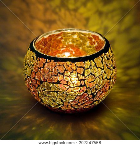 A beautiful candlestick ball of orange and yellow glass with rays of light, with a glowing candle inside