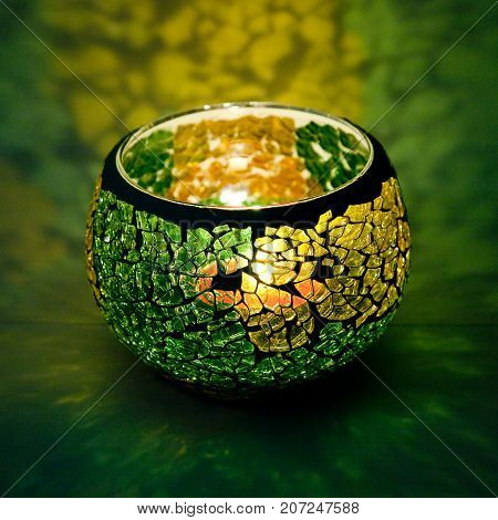 A beautiful candlestick ball of yellow and green glass with rays of light, with a glowing candle inside