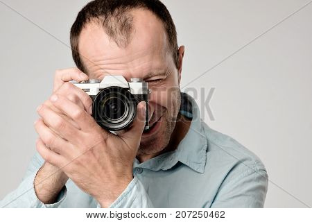 Mature caucasian man in blue t-shirt studing to use digital camera. He is making a shoot