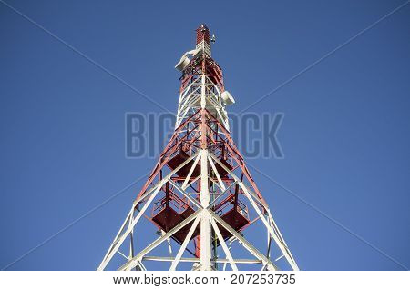 Broadcast relay station antenna over blue sky. Low angle view