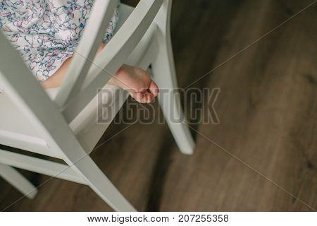 baby leg peeking under a vintage chair