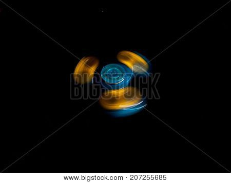 A blue and yellow fidget spinner spins on a black background