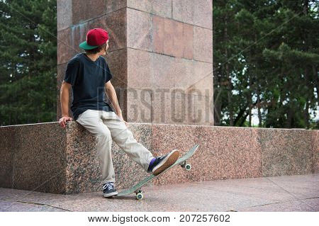 The long-haired skater in a cap and T-shirt sits with his back to the camera and thinks next to the skateboard against the background of the landscape landscape.