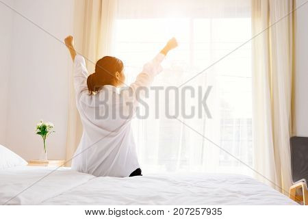 Asian women are waking up in the morning bright. She has a relaxed attitude on the white bed in the bedroom. Along with feeling comfortable weekend.